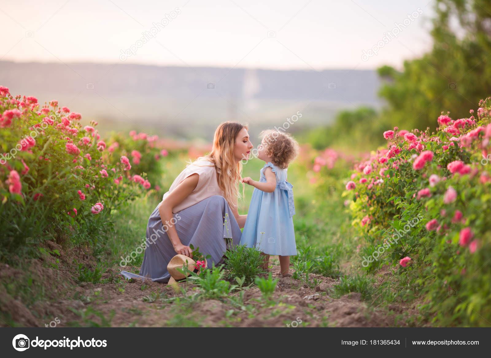 02e191806c Muchacha bonita pareja del niño con la madre están caminando en el jardín  de primavera con