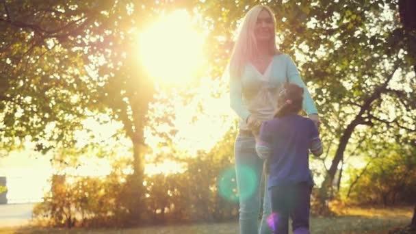 Šťastný matka a dcera v letním parku na sluníčko pozadí v slowmotion. 1920 × 1080
