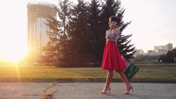Krásná mladá usmívající se žena s nákupní barevné tašky pomocí a diskuse na téma smartphone venku při západu slunce v slowmotion. 1920 × 1080