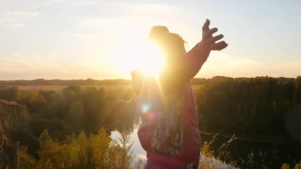 Mature woman standing on the rock rises her hands jumps through the sun and joyful in slowmotion during sunset. 1920x1080