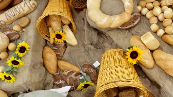 Composition of rye breads, bag of flour and baguettes with sunflowers on the wooden table. Top of view. 3840x2160