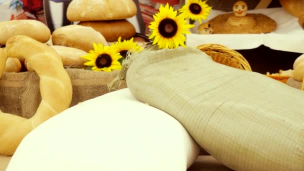 Composition of rye breads, bag of flour, wicker basket and baguettes with sunflowers on wooden table. 3840x2160