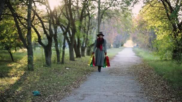 reife elegante Frau im Alter mit Hut und Mantel, bunte Einkaufstaschen in der Hand, Herbstkonzept. 1920x1080