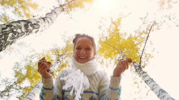 Happy woman wears knitted sweater in autumn park. Joyful and excited young woman having fun throwing yellow leaves in slow motion. 1920x1080