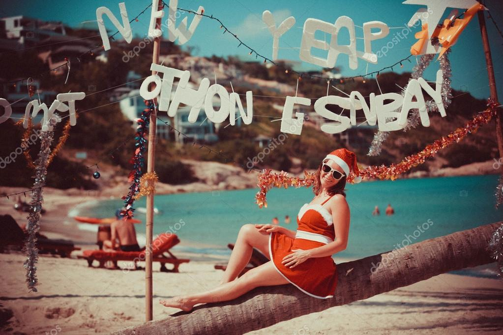 Cute woman in red dress, sunglasses and santa hat sitting on palm tree at exotic tropical beach. Holiday concept for New Years Vintage Cards in retro colors. Koh Samui, Thailand