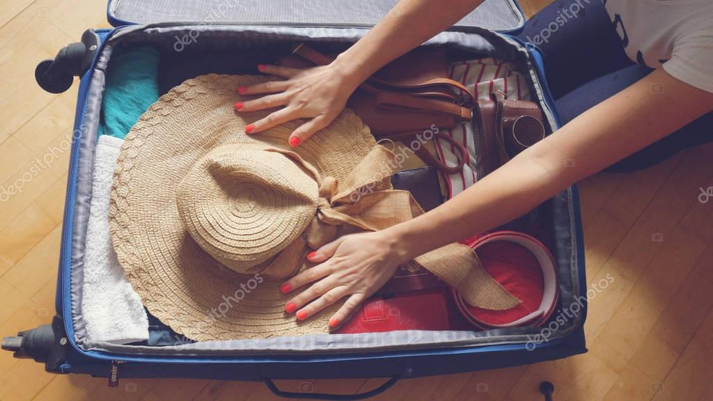Womans hands are packing suitcase for a journey. Retro colors