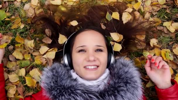 Beautiful happy young woman with headphones lying on autumn leaves listening to music. Season, technology and people concept. 3840x2160