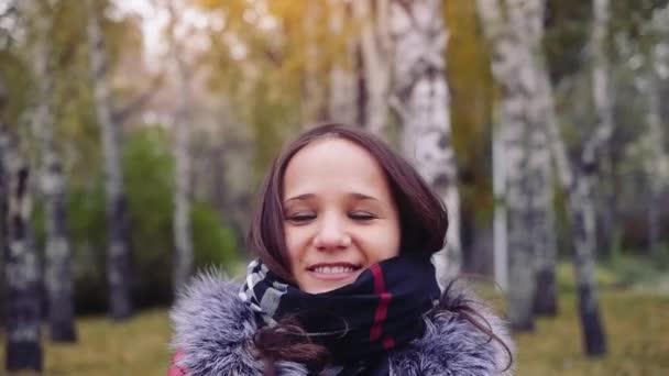 Štěstí ženy relaxační v podzimním parku zvracel listy ve vzduchu s pažemi vztyčenými k slowmotion. 1920 × 1080. krásná dívka v barevné lesní zeleň venkovní