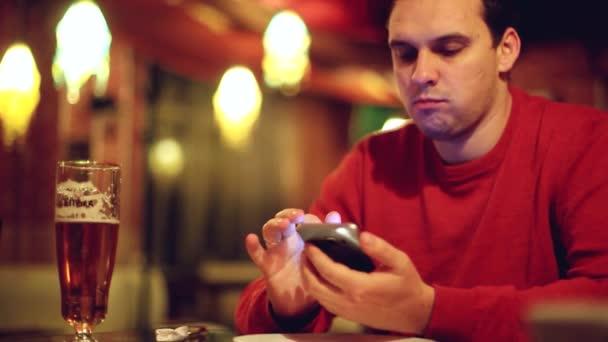 Mladý muž s smartphone, pití piva a čtení nebo odeslání zprávy na bar či hospodu na rozmazané a bokeh pozadím. 1920 × 1080