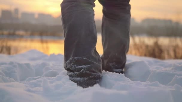 Man traveler trekking in wintertime cold snowy weather, men leg goes over  natural colorful sunset sky with beautiful city background in slowmotion   1920x1080