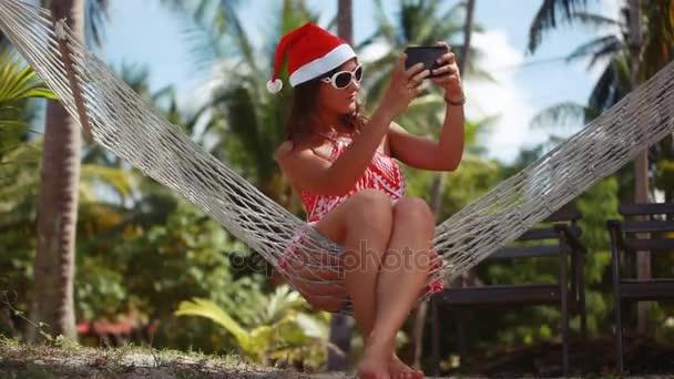 junge schöne Frau mit Sonnenbrille und Weihnachtsmütze in der Hängematte macht Selfie mit dem Handy am tropischen Strand und feiert Weihnachten. 1920x1080