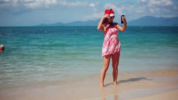 e04b8824 Christmas young slim woman in red santa hat and sunglasses taking picture  self portrait on smartphone at beach over sea background on Koh Samui.  Thailand.