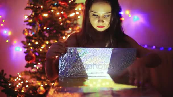 Young happy woman opening the magical Christmas present with magic lights. after open the box girls hair flying. Girl sits next to Xmas tree at decorated home. 1920x1080
