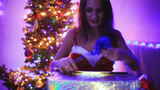 Young joyful beautiful woman opening the magical Christmas present. Girl sits next to Xmas tree at decorated home. 1920x1080