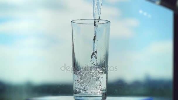 Vylévání vody ve skle v slowmotion rozmazané město a obloha pozadí. 1920 × 1080