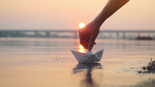 Mans hand putting paper boat on the water and pushing it away during beautiful sunset with reflection sun in the sea in slowmotion, as in childhood. 1920x1080