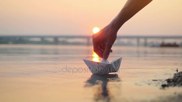 Mans ruku dát papírovou loďku na vodu a odstrčil ji během krásný západ slunce s odraz slunce v moři v vzepjatý, jako v dětství. 1920 × 1080