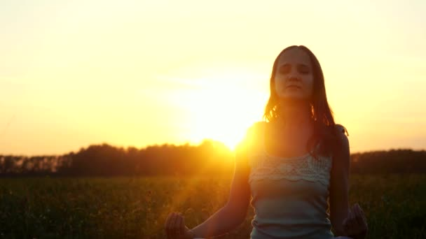 Fiatal gyönyörű barna nő meditál területén során csodálatos naplementét a sun fáklyát hatásokkal. 3840 x 2160