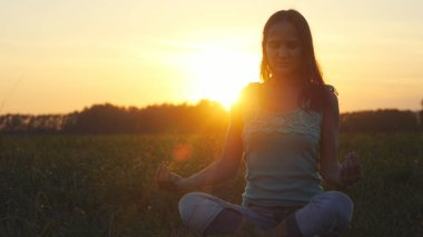 Young beautiful brunette woman meditates in nature, in the field during amazing sunset