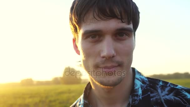 Portrait of handsome man looking at the sun during beautiful sunset with lense flare effects. 3840x2160