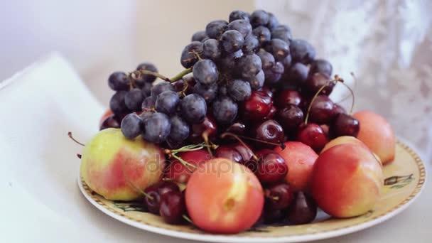 Mans kezében véve a lemez szőlő cseresznye és a meggy- és őszibarack gyümölcs. 1920 x 1080. hd