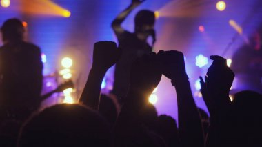 Fans waving their hands at rock concert in night club on beautiful golden lights in a purple colors