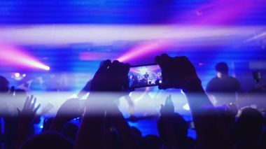 Fans waving their hands recording video and taking pictures with smart phones at music concert. People crowd partying at rock concert in a night club.