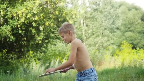 Pohledný mladík hraje raketou míč v přírodě ve zpomaleném filmu. 1920 × 1080