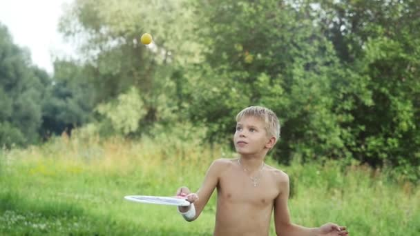 Mladý chlapec hraje raketou míč v přírodě ve zpomaleném filmu. 1920 × 1080