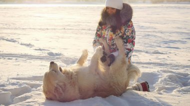 Young beautiful happy girl plays with a retriever dog in the snow in winter in sunny day during sunset time