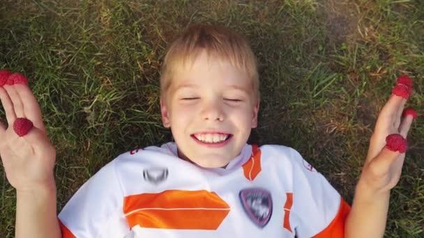 Radostný chlapec ležící na trávě s malinami oblečený na prstech smát a užívat si v létě ve zpomaleném filmu. V horní části zobrazení. 1920 × 1080