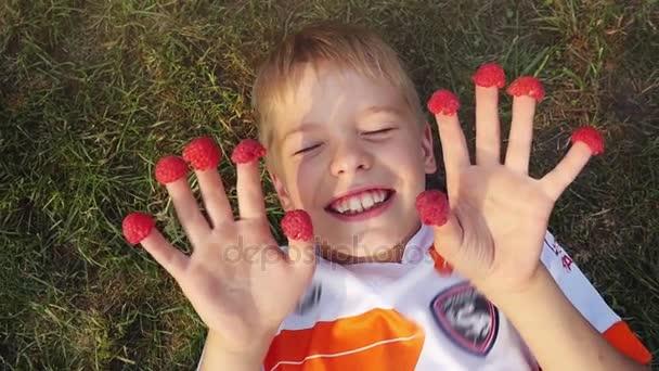 Šťastný, chlapečku, ležící na trávě s malinami oblečený na prstech smát a užívat si v létě ve zpomaleném filmu. V horní části zobrazení. 1920 × 1080