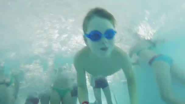 Boy plave pod vodou v bazénu s plavecké brýle přes nohy ostatních lidí. 1920 × 1080