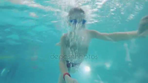 Chlapec se plave pod vodou v bazénu s plavecké brýle. 1920 × 1080