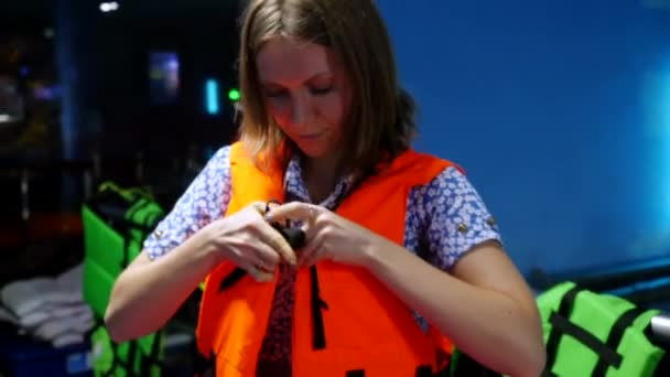 A tourist wears safety vest in in the aquarium before sailing on a boat. 3840x2160