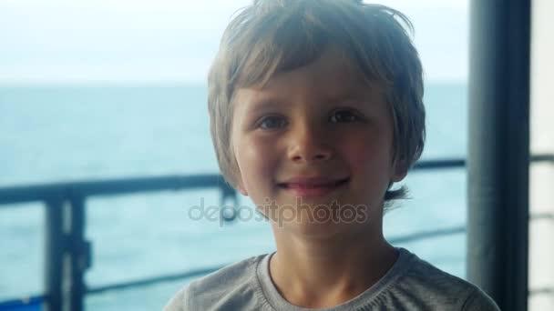 Ein lächelnder kleiner Junge träumt davon, am Wasser zu stehen und am Schiff vorbeizufahren. 3840x2160, 4k