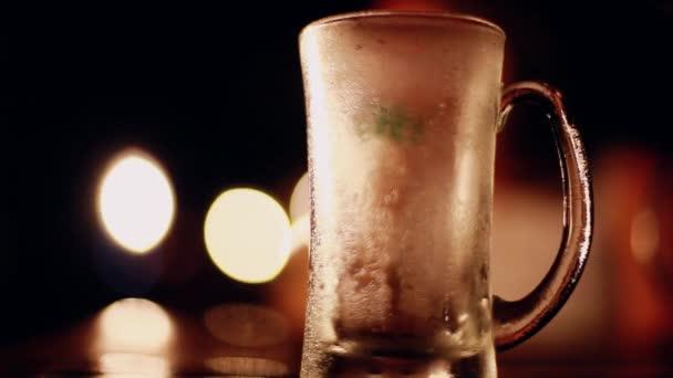 Ömlött be a pohár, az üveg sört. Pohár sör az asztalon, Pub és bár a fények szép bokeh, mint a háttér. 1920 x 1080