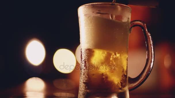 Pivo do sklenice z láhve. Sklenicí piva na stole s kondenzátu na skle v hospodě či baru na krásný bokeh světla jako pozadí. 1920 × 1080