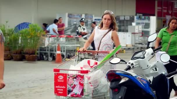 Thailand, Koh Samui, 7 december 2015. Beautiful young women walking on parking lot at supermarket with full shopping cart. 3840x2160