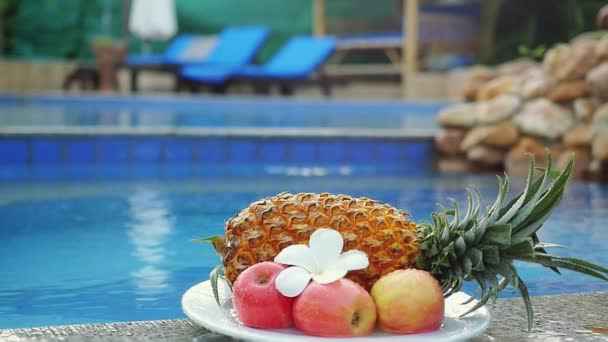 Different fruits pineapple, apples, beautiful frangipani flower are put on the plate on the back of swimming pool changes focus on the pool in slow motion fresh breakfast in Thailand. 1920x1080
