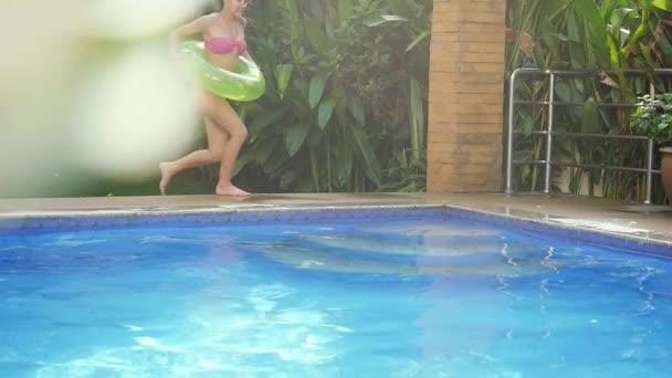 Šťastná Mladá krásná žena s nafukovací kruh vede do bazénu v pomalém pohybu. 1920 × 1080