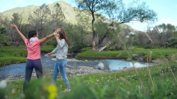 Hikers women cheering happy people huging together in slow motion in beautiful landscape nature with mountains trees and a mountain river. 1920x1080