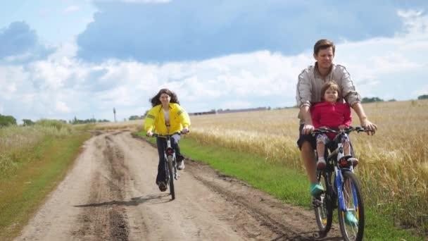 Rusko, Novosibirsk, 20 srpen 2017. Některé jedna šťastná rodina s dítě jedoucí na kole v pole pšenice v letním období v pomalém pohybu. 1920 × 1080