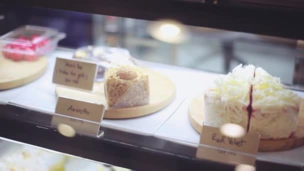 Shop window in a bakery or grocery shop with wide choice or range of various deserts with beautiful blurred bokeh on background. 1920x1080