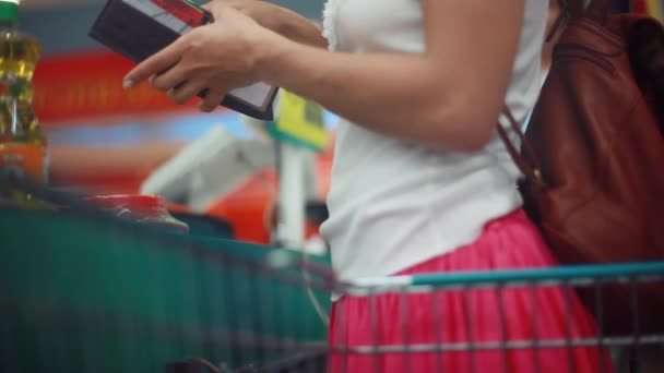 Thailand, Koh Samui, 12 december 2015. Woman with purse buys somethings during christmas holidays. Point of sale. Cashier scans purchase products. 1920x1080, hd