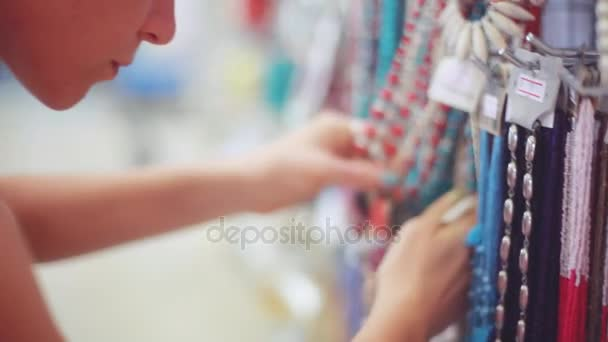 Mladá žena zvolí bižuterie v obchodě šperky na krásný bokeh rozostřeného pozadí. 1920 × 1080