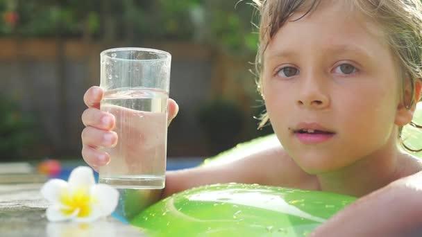 Šťastný chlapec plavání na nafukovací prstenec v bazénu v letní den pije vodu ve zpomaleném filmu. 1920 × 1080