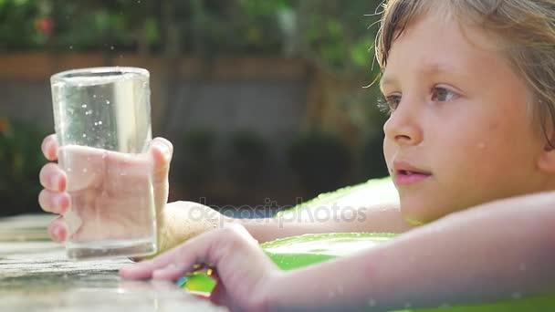 2453b0e84 Niño feliz sonríe poco nadar en anillo inflable en piscina en verano bebe  agua en cámara lenta. 1920 x 1080– metraje de stock