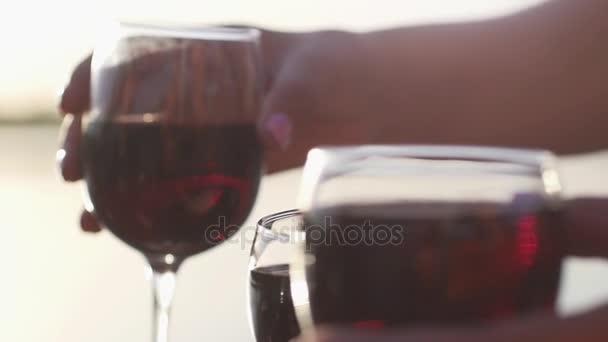 Přátel řinčí poháry plné červené víno v pomalém pohybu u moře při západu slunce. Mají čas odpočinku. 1920 × 1080