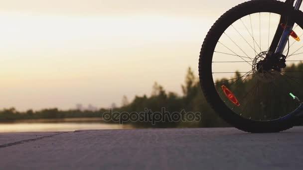 Tlustý muž Cyklistika bycycle na silnici poblíž jezera během krásný západ slunce v pomalém pohybu. 1920 × 1080